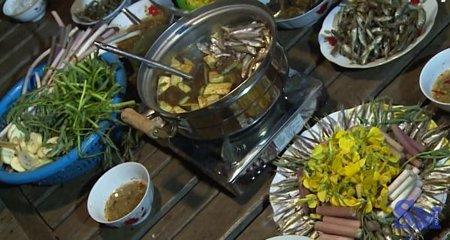 Cho cá linh non vào nồi nước lẩu. Khi nước sôi ùng ục thì gắp cá ra, cho bông điên điển và các loại rau vào